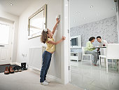 Girl adjusting thermostat in energy efficient house as parents sit in the living room