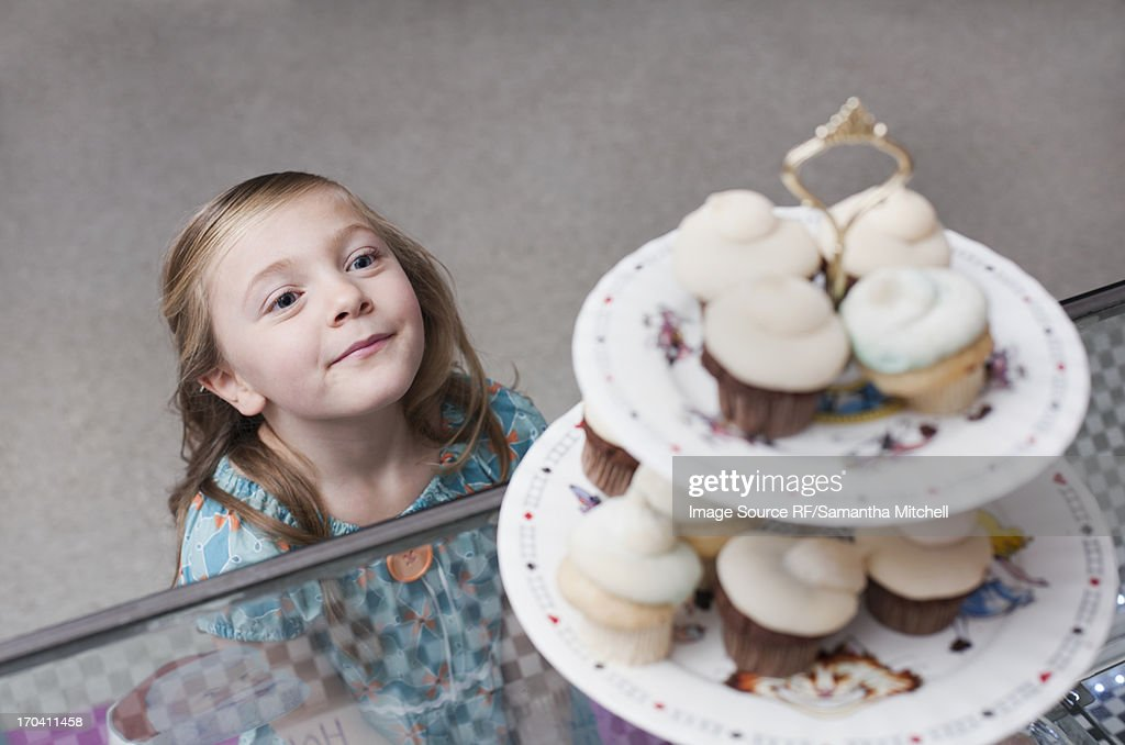 Girl admiring cupcakes in bakery : Stock Photo
