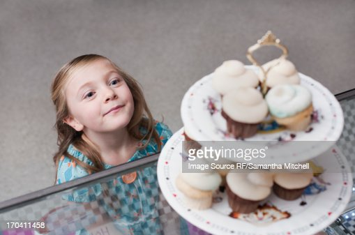 Girl admiring cupcakes in bakery : Stock Photo