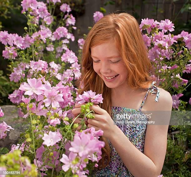 Girl admiring flowers in a garden