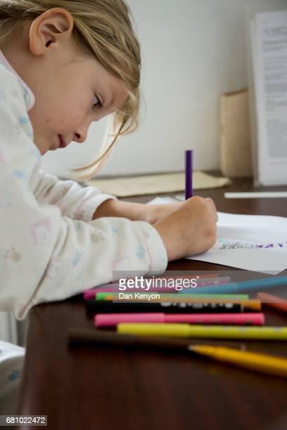 girl aged 6 drawing at table