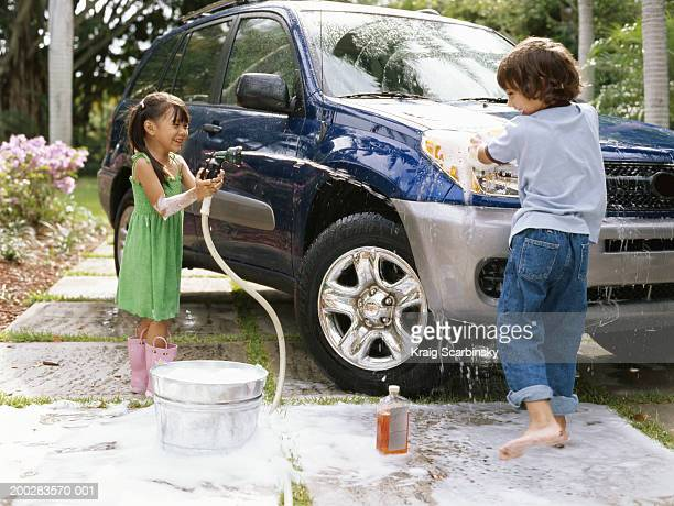 Girl (4-6) aiming hose at boy (5-7) washing car on driveway, smiling