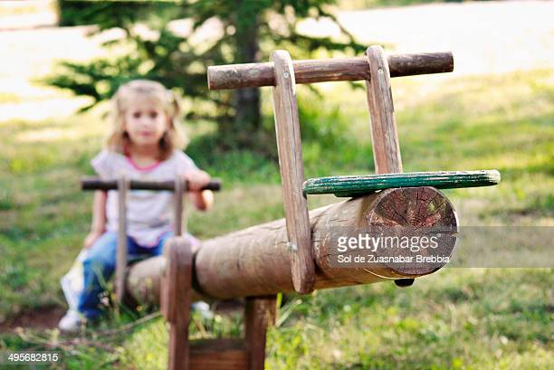 Girl alone on a seesaw empty waiting for company
