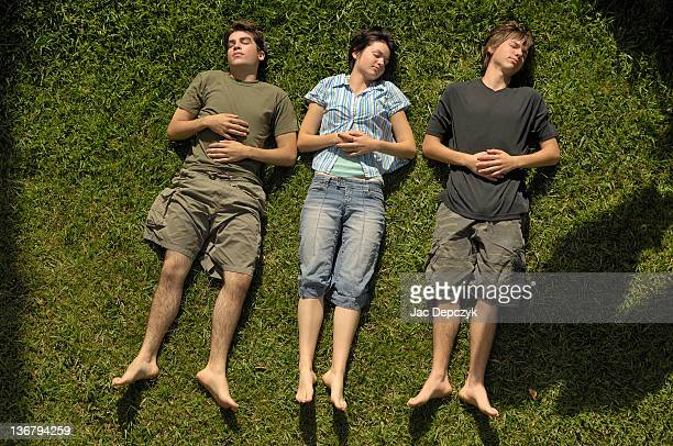 Girl and 2 boys lying on grass doing nothing