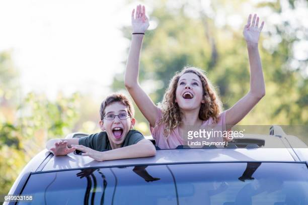 A girl and a boy coming out of the sunroof of a car