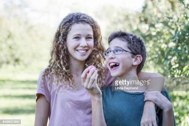 A girl and a boy having fun in a orchard