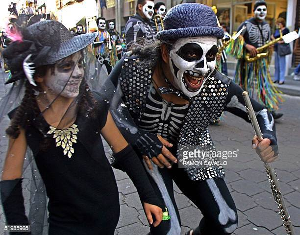 A girl and a man dressed as skeleton dance with musicians during a march in Mexico City 01 November 2001 as part of the 'Day of the Dead' celebration