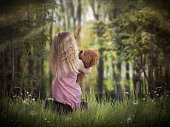 girl and a Teddy bear in the woods to greet the dawn
