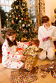 Girl and a teenage girl opening Christmas presents