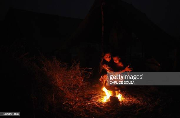 A girl and a young baby are pictured by a fire in a Pakistani armyrun relief camp in Sehwan in the Sindh province on September 15 2010 The Food and...