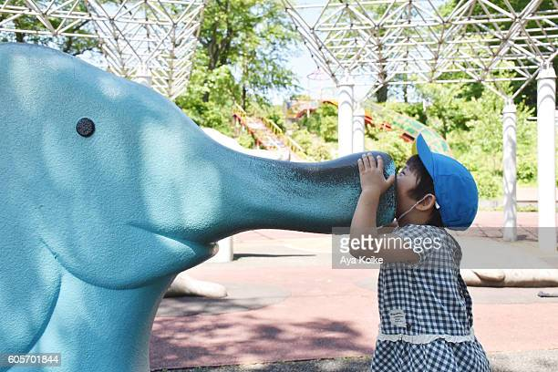 A girl and an elephant playing eqiupment