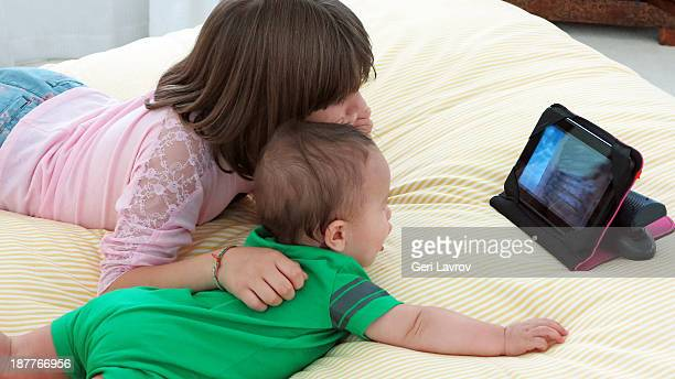 Girl and baby boy looking at a digital tablet