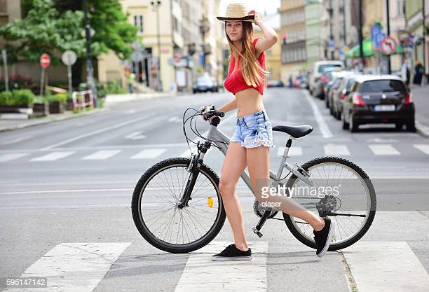 Girl and bicycle in summer city, copy space