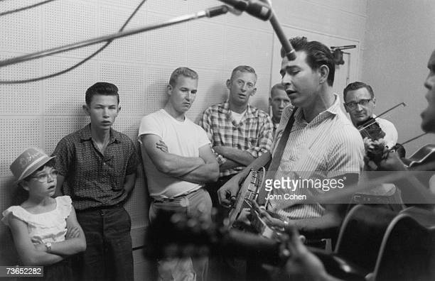 A girl and boy are among those who watch as a bluegrass band performs in a radio station studio Galax Virginia 1961