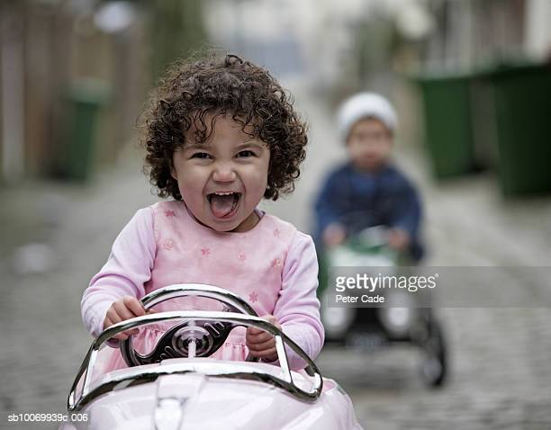 Girl and boy (2-3) driving toy car, focus on girl laughing