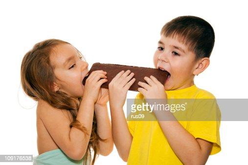 Girl And Boy Eating Chocolate Stock Photo