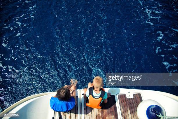 Girl and boy enjoying vacation on sailboat