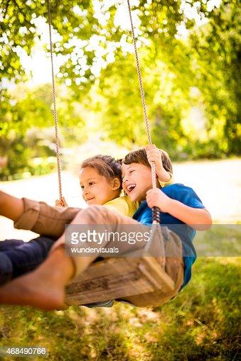 Girl and boy having fun as team to swing high