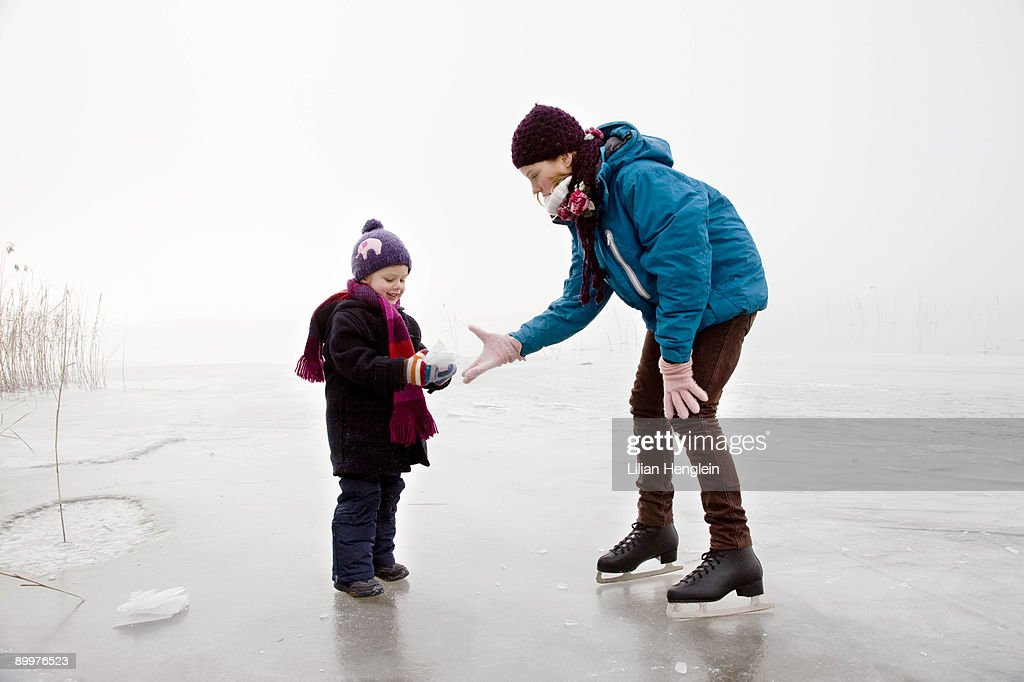Girl and boy iceskating on frozen lake : Stock Photo