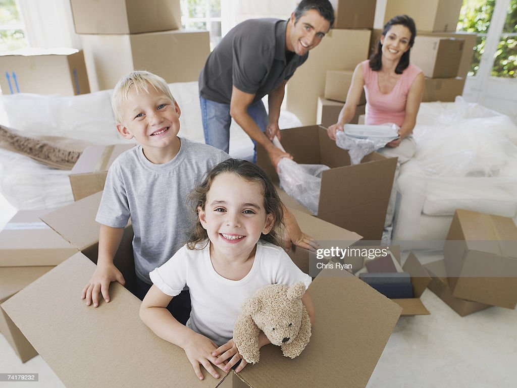 Girl and boy in cardboard box in house with boxes with man and woman in background : Stock Photo