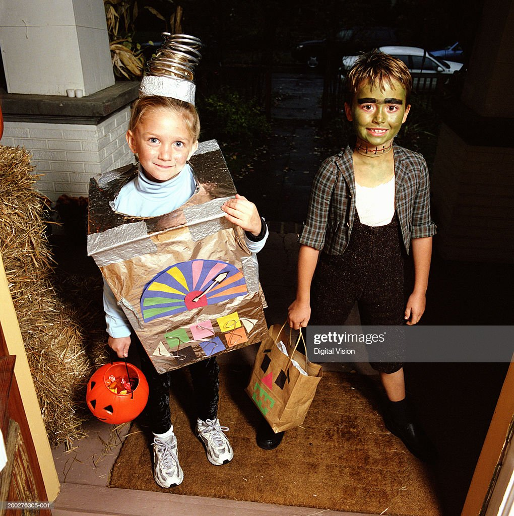 Girl (4-6) and boy (7-9) in costumes standing on doorstep, portrait : Stock Photo