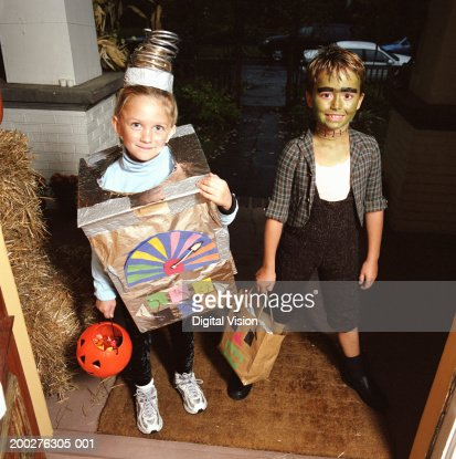 Girl (4-6) and boy (7-9) in costumes standing on doorstep, portrait : Stock-Foto