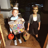 Girl (4-6) and boy (7-9) in costumes standing on doorstep, portrait