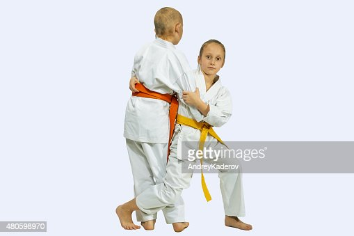 Girl and boy in judogi are training throwing : Stock Photo