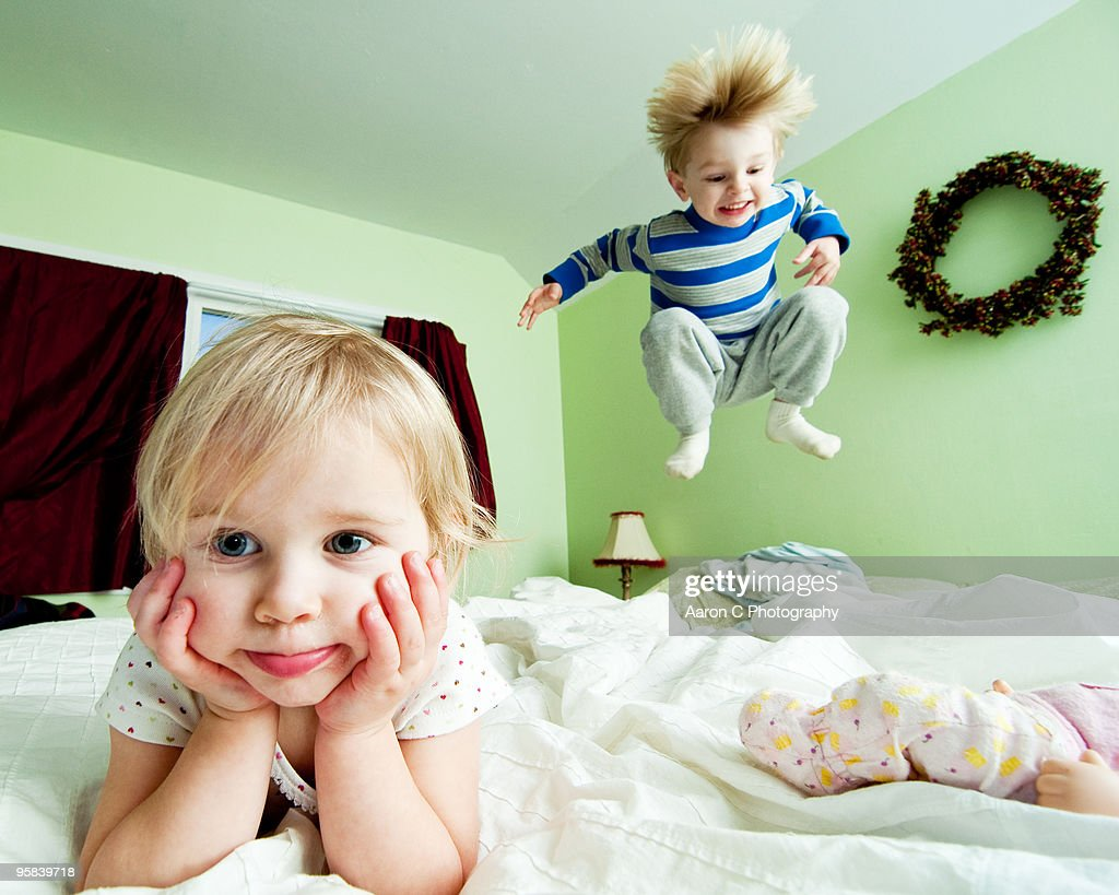Girl and Boy Jump on Bed