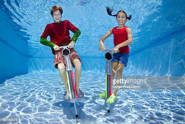 Girl and boy jumping on Pogo Stick underwater