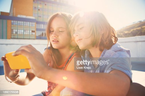 Girl and boy (8-10) looking at smart phone : Stock Photo
