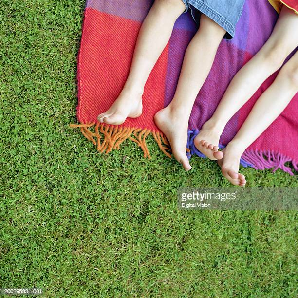 Girl and boy (5-7) lying on blanket on grass, low section