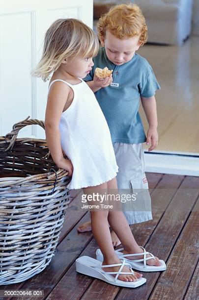 Girl and boy (2-4) on porch, girl wearing adult's sandals