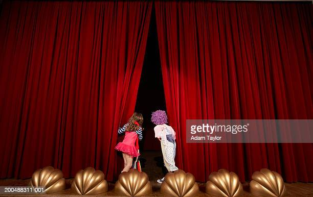 Girl and boy (5-7) on stage, looking through curtains, rear view