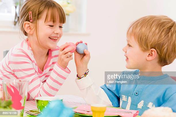 girl and boy painting eggs for easter