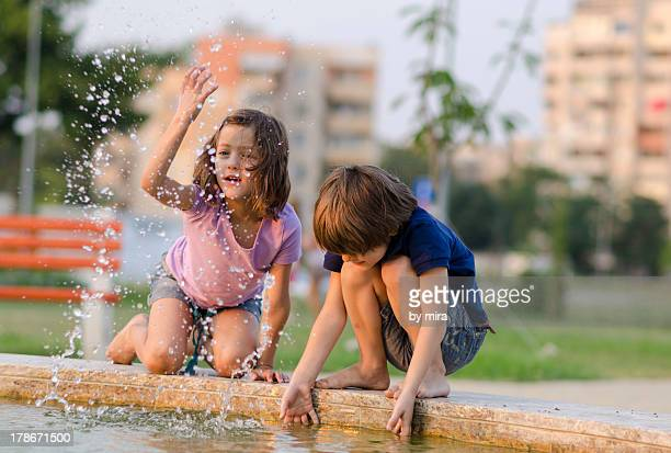 Girl and boy playing at fountain in hot summer