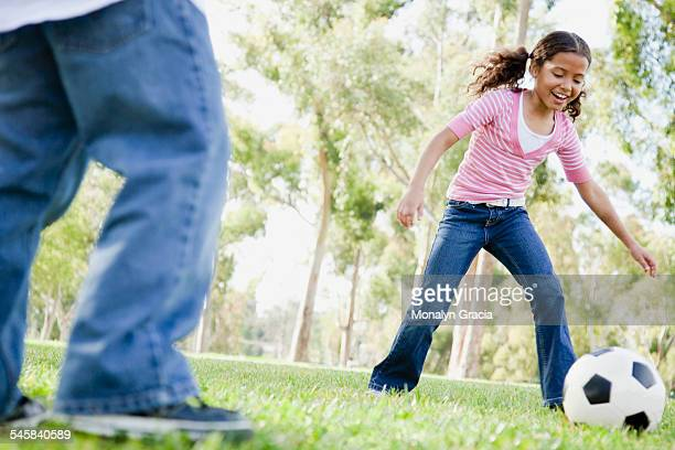 Girl and boy (7-9) playing football in park