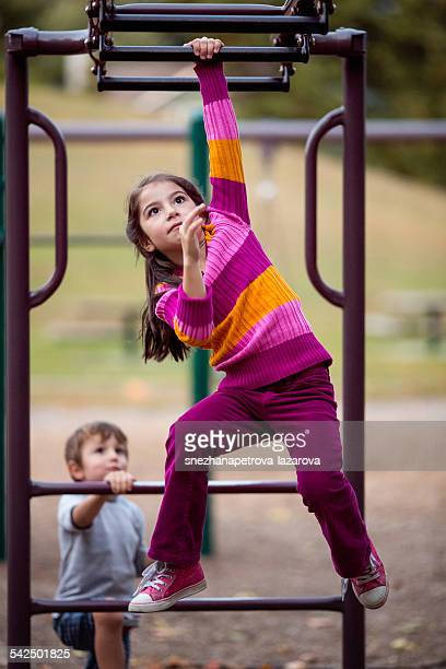 Girl and boy playing on climbing frame