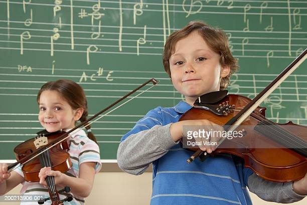 Girl and boy (5-10) playing violins in music class, smiling