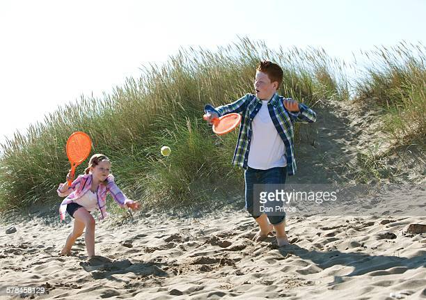 Girl and boy playing with orange sports bat and tennis ball on dunes
