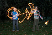 Girl and boy (7-9) playing with sparklers in garden, night