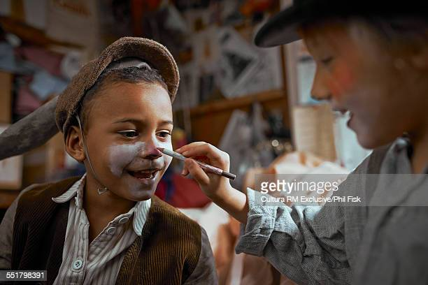 Girl and boy playing with theatre make up backstage