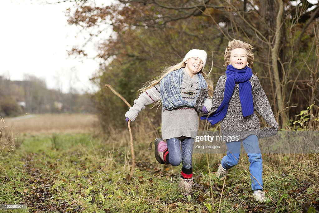 Girl and boy running outdoors : Stock Photo