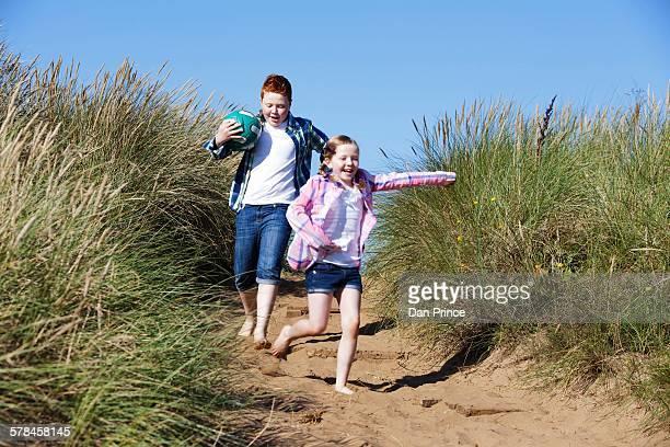 Girl and boy running through marram grass holding football smiling