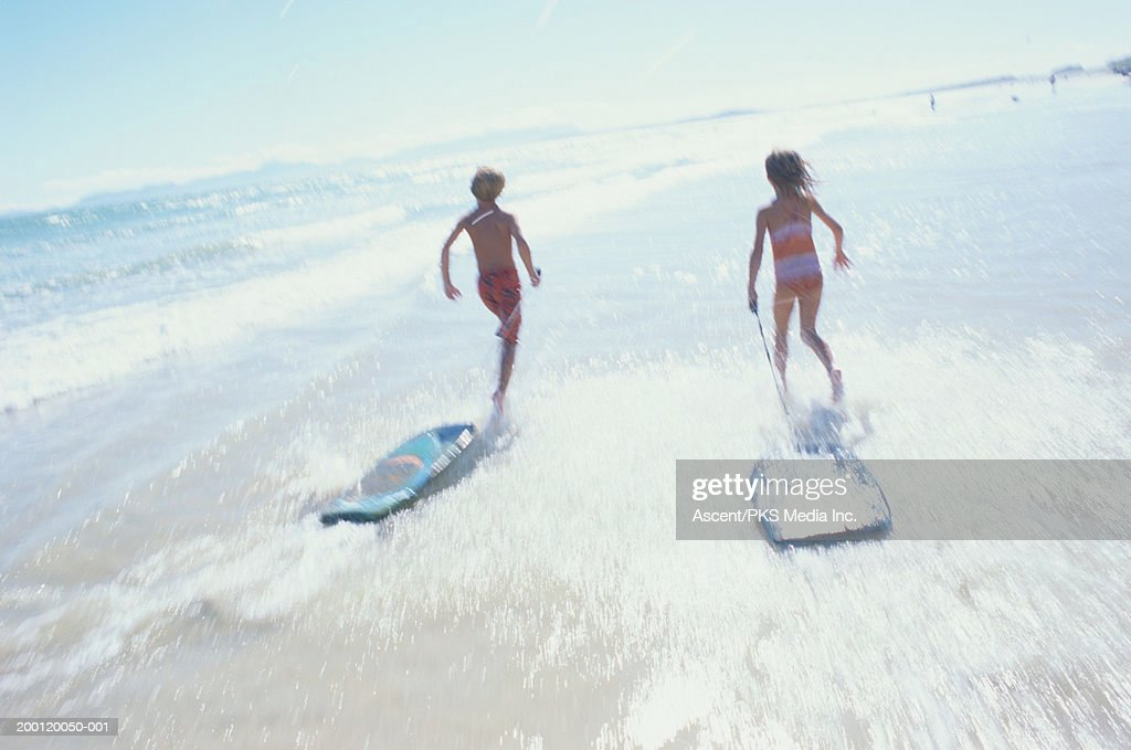 Girl and boy (7-10) running with body boards towards surf : Stock Photo