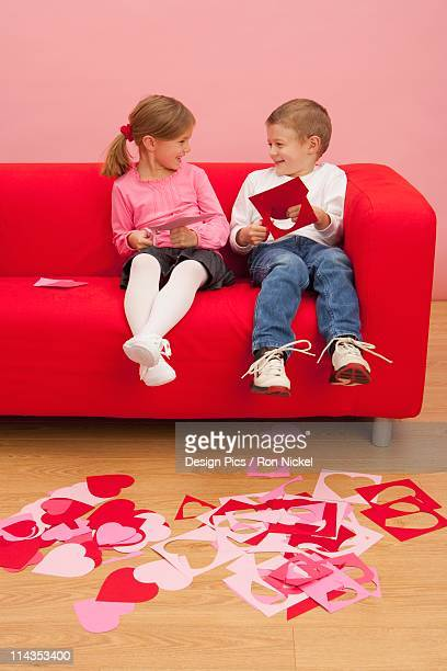 A Girl And Boy Sit On A Couch Cutting Out Hearts