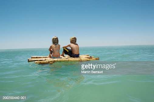 Girl (6-8) and boy (10-12) sitting on bamboo raft in sea, rear view