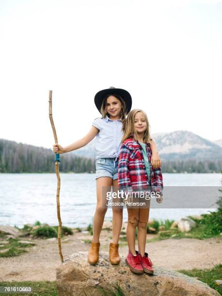 Girl (8-9) and boy (6-7) standing at lakeshore