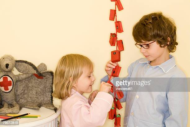 Girl and boy standing by Advent calendar