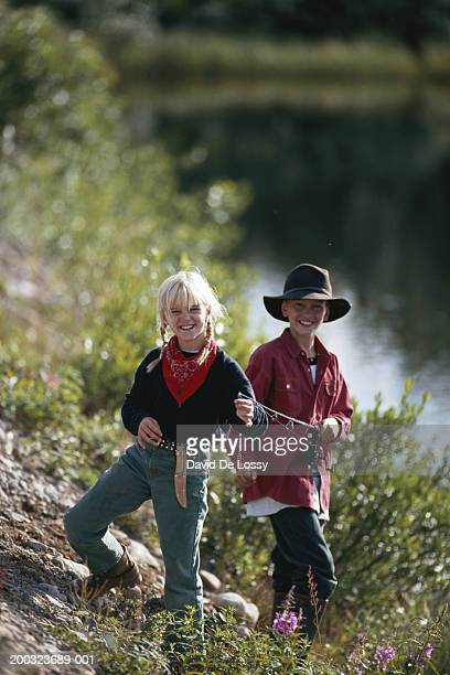 Girl and boy (6-9) standing in forest